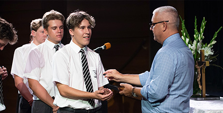 Iona College dean of faith and mission Wayne Wilden presents 3:16 badges to students (The Catholic Leader)