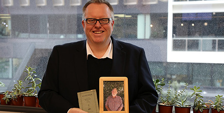 James Anderson with the catechism booklet and a photo of his dad (The Catholic Leader/Joe Higgins)