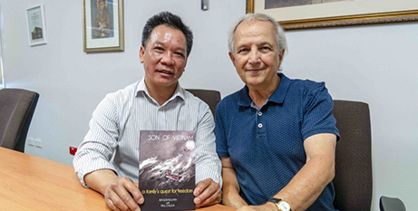 Fr Kim Son Nguyen and Paul Calleja with the book (The eRecord/Matthew Lau)