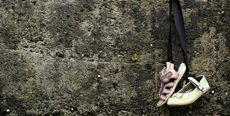 Baby shoes hang on a wall at a cemetery in Tuam, Ireland, where the bodies of nearly 800 infants were uncovered at the site of a former Catholic home for unmarried mothers and their children (CNS/Clodagh Kilcoyne, Reuters)