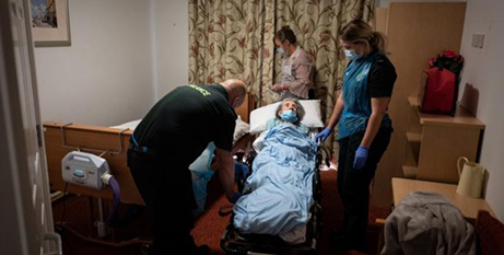 Health care workers with an elderly patient in a nursing home in Portsmouth earlier this month (CNS/Leon Neal, pool via Reuters)
