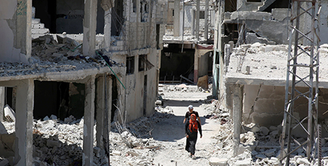 A couple walk past destroyed buildings in Deraa, Syria (CNS/Alaa al Faqir, Reuters)