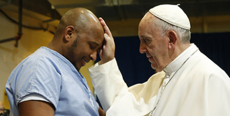 Pope Francis blesses an inmate during a visit to a jail in Philadelphia in 2015 (CNS/Paul Haring)