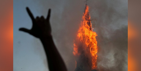A protester gestures while a church burns in Santiago during a demonstration on Sunday against Chile's Government (CNS/Ivan Alvarado, Reuters)