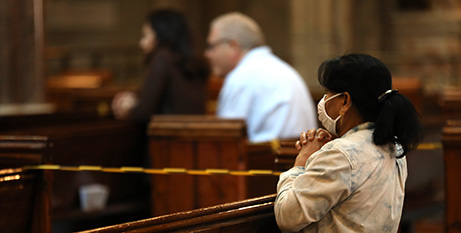 A woman prays during Mass in London in July (CNS/Isabel Infantes, PA Images vis Reuters)