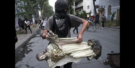 A masked demonstrator with a statue of Jesus he took from a church in Santiago on Friday (Crux/Esteban Felix, AP)