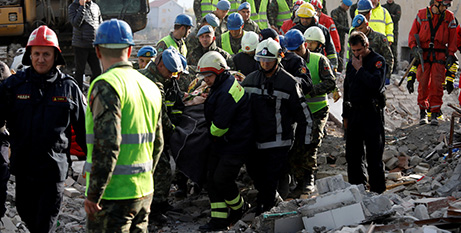 Emergency personnel carry the body of a victim in Thumane, Albania, yesterday after a magnitude 6.4 earthquake struck on Tuesday (CNS/Florion Goga, Reuters)