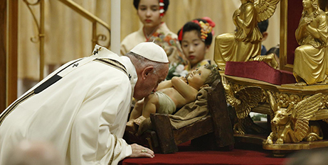 Pope Francis kisses a figurine of the baby Jesus as he arrives to celebrate the 2019 Christmas Eve Mass in St Peter's Basilica (CNS/Paul Haring)